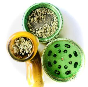 bowl with strains in green metallic grinder